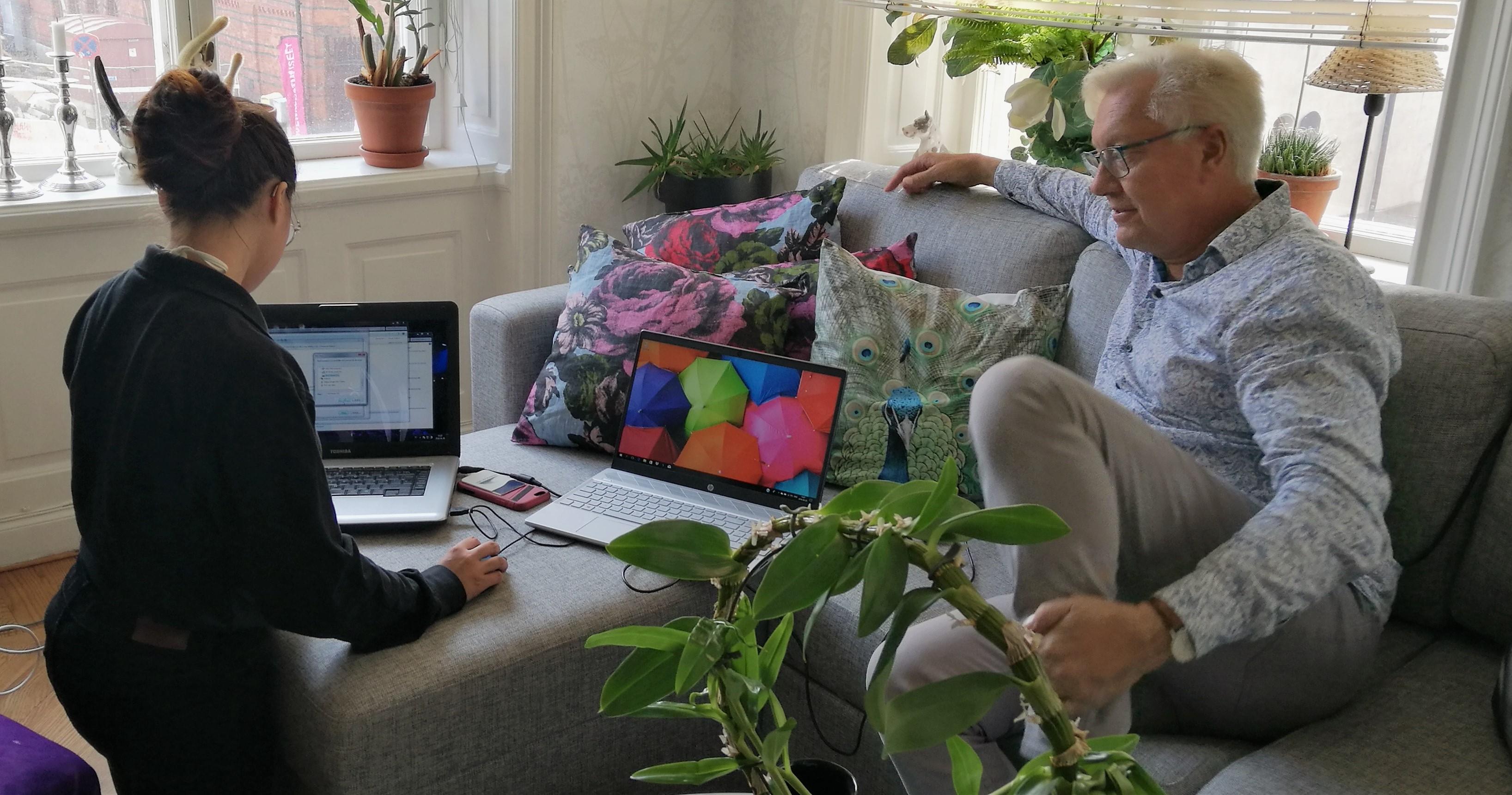 Lars Åke Wilhelmsson sitter i en soffa och tittar på med en tekniker fixar hans dator.